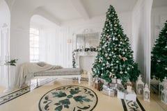 Mañana de la Navidad apartamentos de lujo clásicos con una chimenea blanca, árbol adornado, sofá brillante, ventanas grandes Imágenes de archivo libres de regalías