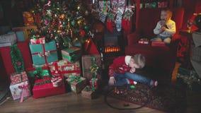 Mañana de la Navidad Dos muchachos cerca de un árbol de navidad miran sus regalos almacen de video