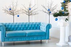 Mañana de la Navidad, espacio de la copia Apartamentos clásicos con el sofá abotonado azul, árbol de abeto adornado imagen de archivo