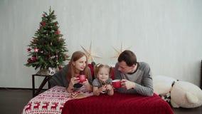 Mañana de la Navidad La familia joven juega feliz con uno a En la cama muchas almohadas, regalos de la Navidad adentro almacen de video