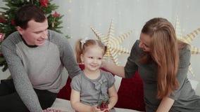 Mañana de la Navidad La familia joven juega feliz con uno a En la cama muchas almohadas, regalos de la Navidad adentro metrajes