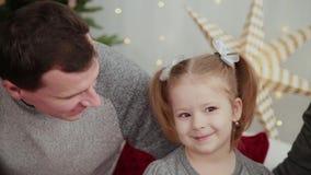 Mañana de la Navidad La familia joven juega feliz con uno a En la cama muchas almohadas, regalos de la Navidad adentro almacen de metraje de vídeo