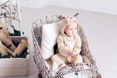 Mañana de la Navidad Niña en los ciervos del mono que se sientan en un trineo largo Foto de archivo
