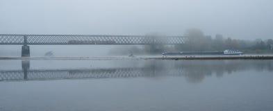 Mañana de niebla del otoño en Alemania en el río el Rin, el fluir barge adentro la distancia un puente ferroviario viejo imagenes de archivo