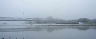 Mañana de niebla del otoño en Alemania en el río el Rin, el fluir barge adentro la distancia un puente ferroviario viejo foto de archivo libre de regalías