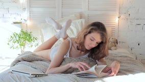 Mañana de una mujer joven hermosa, ella que lee un libro que miente en cama almacen de metraje de vídeo