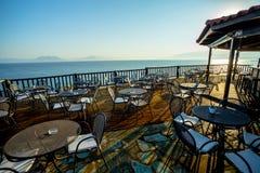 Mañana del comienzo del verano en la terraza de madera con la vista del mar foto de archivo libre de regalías