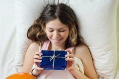 Mañana del cumpleaños Adolescente que miente en cama en la almohada que sostiene un regalo, visión superior Fotografía de archivo libre de regalías