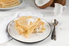 Mañana, desayuno - crepes rusas tradicionales del blini, crespones franceses, coco fresco, botella de leche, jarra de cerámica  imagen de archivo