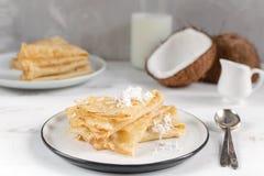Mañana, desayuno - crepes rusas tradicionales del blini, crespones franceses, coco fresco, botella de leche, jarra de cerámica  foto de archivo libre de regalías