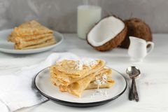 Mañana, desayuno - crepes rusas tradicionales del blini, crespones franceses, coco fresco, botella de leche, jarra de cerámica  fotografía de archivo