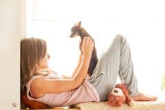 Mañana dulce Chica joven en los pijamas que sostienen su perro precioso Imagen de archivo