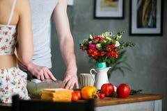 Mañana en la cocina Pares jovenes que preparan la comida fotos de archivo