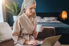 Mañana La mujer joven en albornoz y toalla en su cabeza se sienta en sitio en el sofá, bebe el café y utiliza el ordenador portát imagen de archivo libre de regalías