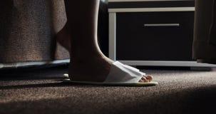 Mañana, los pies femeninos hermosos consiguen abajo de puntillas de cama Señora descalza femenina despierta temprano en dormitori metrajes