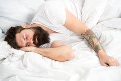 Mañana perezosa Inconformista barbudo del hombre soñoliento en cama Horas de la madrugada Problemas del insomnio y del sueño Relá fotografía de archivo