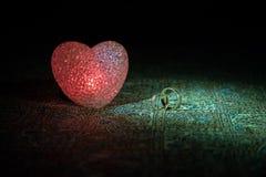 Małżeństwo propozycja z złocistymi obrączkami ślubnymi i sercem pojęcia serce nad czerwieni różanym valentine biel Zmroku stonowa Obrazy Stock