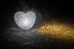 Małżeństwo propozycja z złocistymi obrączkami ślubnymi i sercem pojęcia serce nad czerwieni różanym valentine biel Zmroku stonowa Zdjęcie Royalty Free