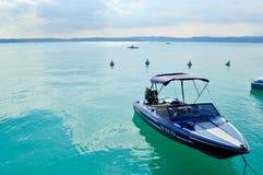 Mała łódka na błękitnym jeziorze w pogodnym letnim dniu z jasnym niebieskim niebem Obrazy Stock