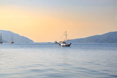 Mała łódka na morzu z górami Zdjęcia Royalty Free