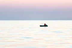 Mała łódka w morzu przy wschodem słońca obraz stock