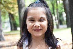 Mała łacińska dziewczyna śmia się w parku Fotografia Stock