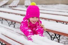 Mała ładna dziewczyna bawić się z śniegiem Zdjęcia Royalty Free
