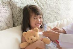 Mała ładna dziewczyna przy lekarką - pracownik służby zdrowia sprawdza on obrazy stock