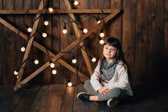 Mała ładna dziewczyna siedzi na tle nowego roku ` s gwiazda zdjęcia royalty free