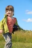 Mała ładna dziewczyna trzyma kamerę i patrzeje daleko od przy łąką Obrazy Royalty Free