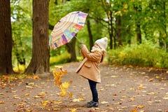 Mała ładna dziewczyna w beżowym żakiecie, jesień w parkowym miotaniu zdjęcia royalty free