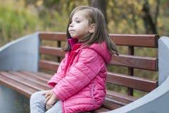 Mała ładna dziewczyna w różowym żakieta obsiadaniu na drewnianej ławce przy parkiem w jesieni portret emocjonalny Dzieciństwa poj fotografia stock