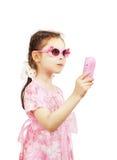 Mała ładna dziewczyna z różowymi okularów przeciwsłonecznych chwytami bawi się wiszącą ozdobę Fotografia Stock