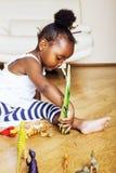 Mała śliczna amerykanin afrykańskiego pochodzenia dziewczyna bawić się z zwierzęciem bawi się przy ho Fotografia Royalty Free