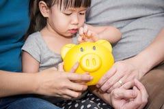 Mała śliczna azjatykcia dziewczyna stawia monetę w jej żółtym prosiątko banku Fotografia Royalty Free