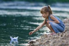 Mała śliczna blond długowłosa dziewczyna w błękit sukni na riverbank otoczakach bawić się z białego papieru origami łodzią na błę Zdjęcia Stock