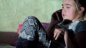 Mała śliczna blond dziewczyna opowiada na telefonu komórkowego obsiadaniu na kanapie w mieszkaniu zbiory