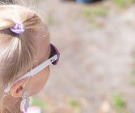 Mała śliczna blond dziewczyna w okulary przeciwsłoneczni fotografia royalty free