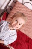Mała śliczna blond dziewczyna w pasiastym koszulowym obsiadaniu wśród czerwonej poduszki Zdjęcia Stock
