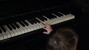 Mała śliczna chłopiec delikatnie naciska jeden pianino klucz w zwolnionym tempie zdjęcie wideo