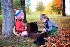 Mała śliczna chłopiec i dziewczyna bawić się w jesień parku Obraz Stock