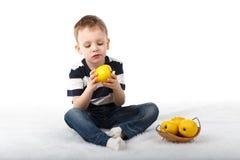 Mała śliczna chłopiec je żółtego jabłka i ono uśmiecha się na białym backg Zdjęcia Royalty Free