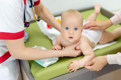 Mała śliczna chłopiec odwiedza lekarkę Pediatra robi czekowi up i egzamininujący niemowlaka dla choroby zapobiegania protokołu zdjęcia stock