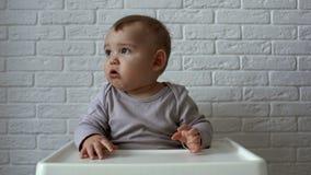Mała śliczna chłopiec siedzi przy dziecko stołem i je ciastka zbiory wideo