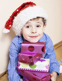 Mała śliczna chłopiec z Bożenarodzeniowymi prezentami w domu zamyka w górę emocjonalnej twarzy na pudełkach w Santas czerwonym ka obraz stock
