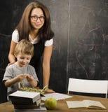 Mała śliczna chłopiec z nauczycielem w sala lekcyjnej Fotografia Stock