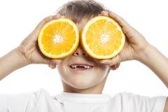 Mała śliczna chłopiec z pomarańczową owoc kopią odizolowywającą na biały ono uśmiecha się bez frontowych zębów uroczego dzieciaka Obraz Stock