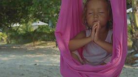 Mała śliczna dziecko dziewczyna robi joga exersice z hamakiem na plaży zdjęcie wideo