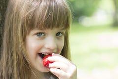 Mała śliczna dziewczyna je soczystego strawberr z piękną twarzą Zdjęcie Stock