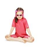 Mała śliczna dziewczyna jest ubranym menchii ubrania siedzi jak jogów Fotografia Stock